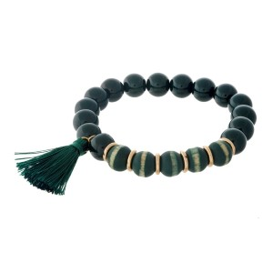 Hunter green beaded stretch bracelet with wooden beads and a tassel accent.