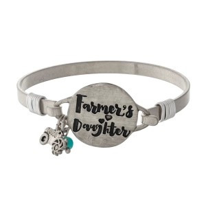 """Metal bangle bracelet with a circle focal stamped with """"Farmer's Daughter."""""""