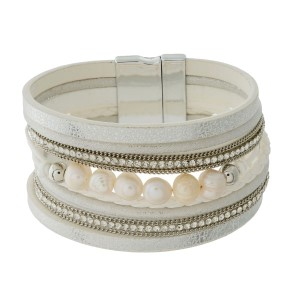 Faux leather bracelet with clear rhinestones, freshwater pearl beads, and a silver tone magnetic closure.