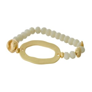 Beaded stretch bracelet with a matte gold tone circle focal.