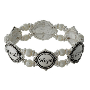 "Pearl beaded stretch bracelet with silver tone shapes, stamped with ""Faith, Hope, Love."""