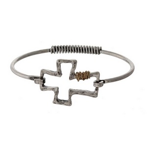 Dainty, metal bangle bracelet with an open cross focal and wire wrapping accents.