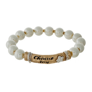 "Pearl and gold tone beaded stretch bracelet with a bar focal stamped with ""Choose Joy."""