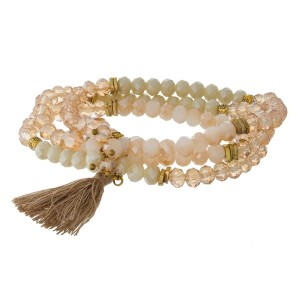 Three row, stretch bracelet with gold tone and tassel accents.