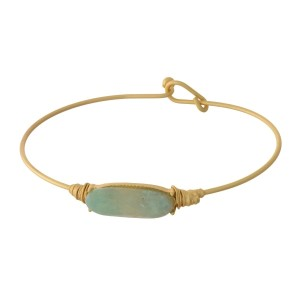 Dainty gold tone bangle bracelet with a natural, oval stone focal. This is a natural stone and colors may vary.