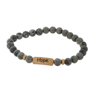 """Natural stone beaded stretch bracelet with a gold tone focal stamped with """"Hope."""""""