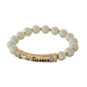 """Pearl beaded stretch bracelet with a gold tone bar focal, stamped with """"Sisters."""""""
