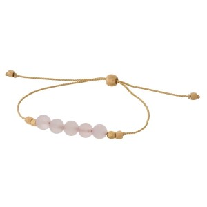 Gold tone, pull-tie bracelet with natural stones.