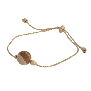 Gold tone, pull-tie bracelet with a natural stone bead. Natural stone colors may vary.