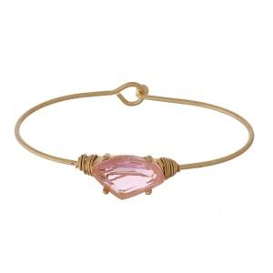 Dainty gold tone bangle bracelet with a rhinestone focal.