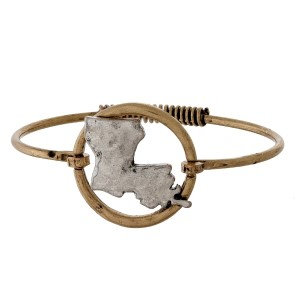 Burnished gold tone bangle bracelet with a silver tone state focal and a hammered texture.