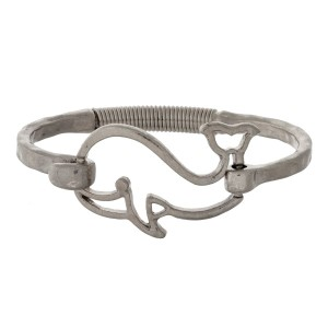 Hammered metal bangle bracelet with a whale focal and a hinge closure.