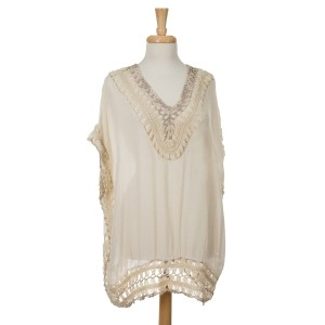 Beige short sleeve top with crochet detailing. Top is sewn all the way down to the bottom hem. 35% acrylic and 65% viscose. One size fits most.