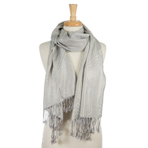"""Gray lightweight scarf with metallic silver threaded details and tassels on the ends. 55% polyester and 45% viscose. Measures 26"""" x 72"""" in size."""