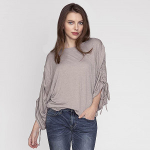 One size top with oversized sleeves that can be adjusted in length from long sleeve to short sleeve. 35% viscose and 65% polyester. One size fits most.