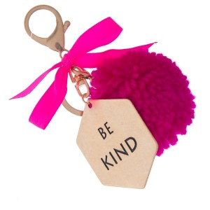 """Gold tone key chain or bag charm stamped with """"Be Kind"""" and a fuchsia pom pom. Approximately 5.5"""" in length."""