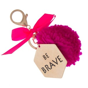 """Gold tone key chain or bag charm stamped with """"Be Brave"""" and a fuchsia pom pom. Approximately 5.5"""" in length."""