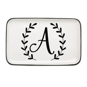 "White ceramic trinket tray featuring a script 'A' initial with black trim. Measures approximately 6.5"" x 4"" in size."