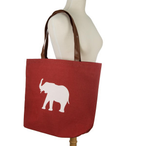 "Crimson tote bag with a white elephant design, a flat bottom and faux leather handles. Measures 18"" x 12"" with a 9"" shoulder drop."