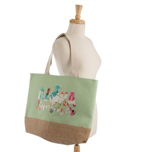 """Aloha Summer"" tote bag with a fully lined interior, magnetic closure, and inside pocket. Measures 20"" x 15"" in size with a 10"" shoulder drop. 55% cotton, 25% polyester, and 20% jute."