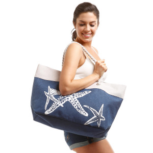 """Canvas tote bag with a starfish pattern, top zipper closure, rope handles and a lining inside with pockets. 35% cotton and 65% polyester. Measures 21"""" x 15"""" in size."""