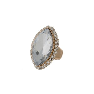 Gold tone stretch ring with a clear oval faceted stone.