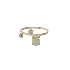 Gold tone ring with a green stone, accented by rhinestones. Approximately a size 7.